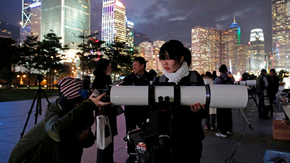 People use telescopes to view the moon at Victoria Harbor in Hong Kong.