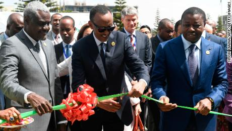 Rwandan President and Chairperson of the African Union, Paul Kagame (C) flanked by Togo President Faure Gnassingbe (R) and Chairperson of African Union Commission Moussa Faki Mahamat, cuts a ribbon during a launch of the Single African Air Transport Market at the 30th Ordinary Session of the African Union (AU) Summit in Addis Ababa, 29 January 2018. The Single African Air Transport Market provides full liberalization of market access between African States, free exercise of traffic rights, elimination of restrictions on ownership and full liberalization of frequencies, fares and capacities. / AFP PHOTO / SIMON MAINA        (Photo credit should read SIMON MAINA/AFP/Getty Images)