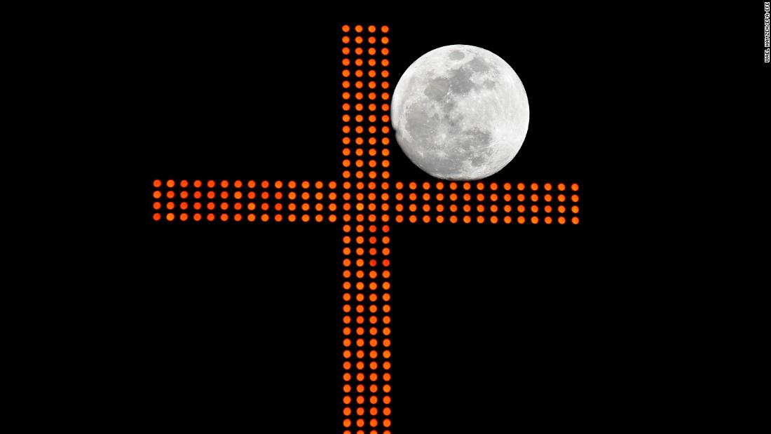 The supermoon is framed by a cross in Beirut, Lebanon.