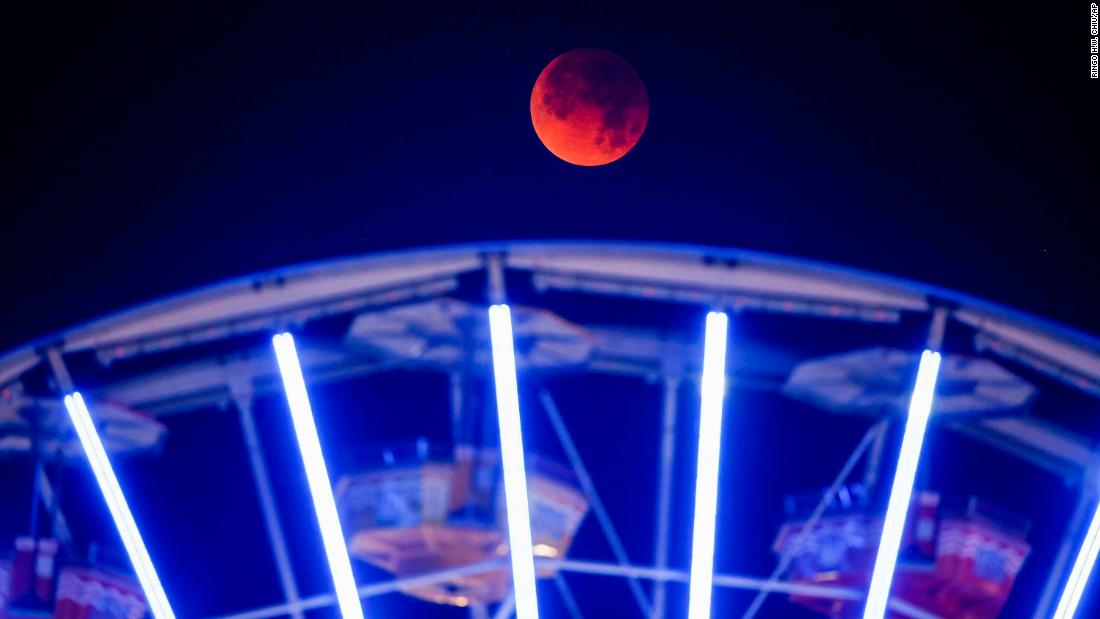 The moon is seen behind a Ferris wheel at Santa Monica Beach in Santa Monica, California.