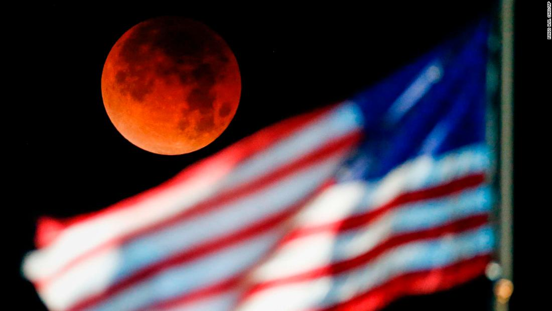 The supermoon is seen behind the US flag at Santa Monica Beach in Santa Monica, California.