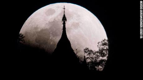 TOPSHOT - The moon rises over a pagoda in Kumal, some 105 kms away from Mandalay City, Myanmar on January 31, 2018.  Skywatchers were hoping for a rare lunar eclipse that combines three unusual events -- a blue moon, a super moon and a total eclipse -- which was to make for a large crimson moon viewable in many corners of the globe. / AFP PHOTO / YE AUNG THU        (Photo credit should read YE AUNG THU/AFP/Getty Images)