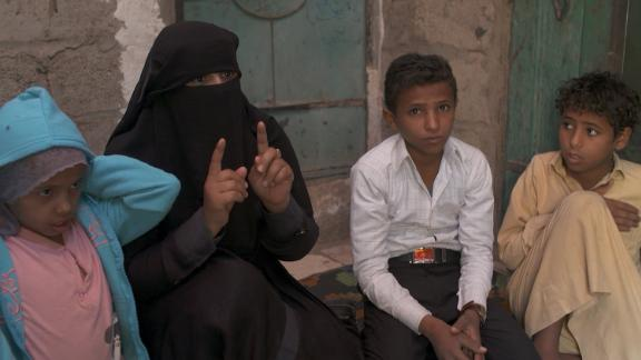 Ex-child soldier Younis, 13 (second from right), and his mother Samira speak about the boy