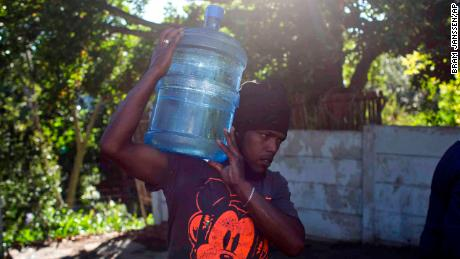 "A man carries water at a source for natural spring water in Cape Town, Thursday, Feb. 1, 2018. South Africa's drought-hit city of Cape Town plans to introduce new water restrictions on Thursday in an attempt to avoid what it calls ""Day Zero,"" the day in mid-April when it might have to turn off most taps. Residents will be asked to use no more than 50 liters of water daily, down from the current limit of 87 liters. (AP Photo/Bram Janssen)"