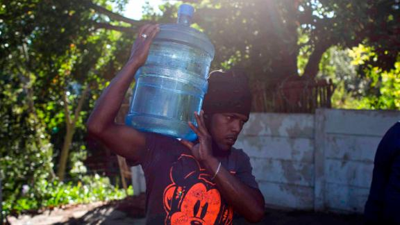 A man in Cape Town, South Africa, carries water from a natural spring on Thursday, February 1.