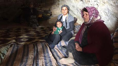 Afrin residents sit on blankets carpeting the floor of a cave.