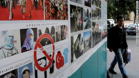 Pedestrians walk past anti-terror propaganda posters pasted along the streets of Urumqi,  September 2014.