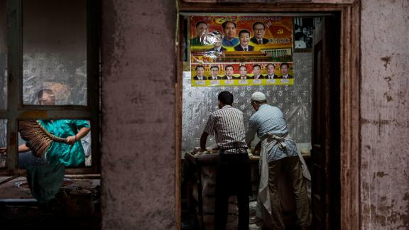 KASHGAR, CHINA - JULY 1: Under a poster showing Chinese leaders including the late Mao Zedong and the present President Xi Jinping, ethnic Uyghur men make bread at a local bakery on July 1, 2017 in the old town of Kashgar, in the far western Xinjiang province, China. Kashgar has long been considered the cultural heart of Xinjiang for the province's nearly 10 million Muslim Uyghurs. At an historic crossroads linking China  to Asia, the Middle East, and Europe, the city has  changed under Chinese rule with government development, unofficial Han Chinese settlement to the western province, and restrictions imposed by the Communist Party. Beijing says it regards Kashgar's development as an improvement to the local economy, but many Uyghurs consider it a threat that is eroding their language, traditions, and cultural identity.  The friction has fuelled a separatist movement that has sometimes turned violent, triggering a crackdown on what China's government considers 'terrorist acts' by religious extremists.  Tension has increased with stepped up security in the city and the enforcement of measures including restrictions at mosques. (Photo by Kevin Frayer/Getty Images)