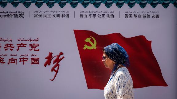 A Uyghur woman passes the Communist Party of China flag on a wall in Urumqi, the provincial capital of Xinjiang, in western China, June 2017.