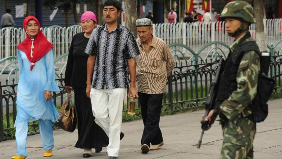 A Chinese paramilitary policeman watches as an ethnic Uyghur family walks in front of Urumqi's Grand Bazaar, July, 2009.