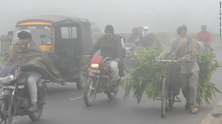Indian commuters make their way through heavy smog in Amritsar in November, 2017.