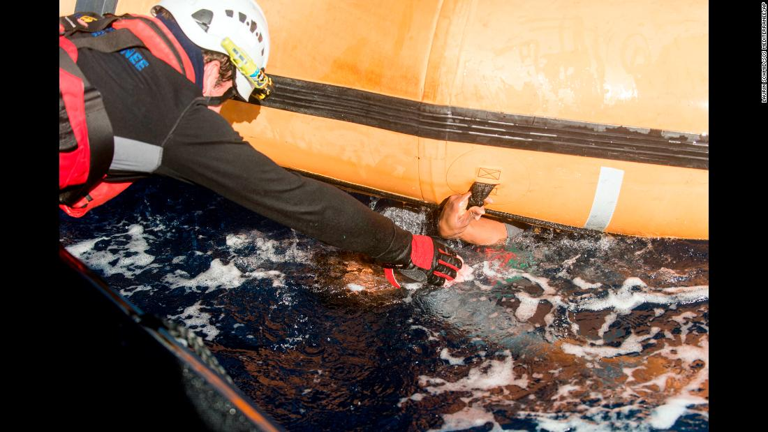 "A rescuer reaches for the hand of a man who was holding onto a dinghy in the Mediterranean Sea on Saturday, January 27. About 800 migrants were rescued from five boats, the Italian coast guard said. Two bodies were also recovered. <a href=""http://www.cnn.com/2015/09/03/world/gallery/europes-refugee-crisis/index.html"" target=""_blank"">Europe's migration crisis in 25 photos</a>"
