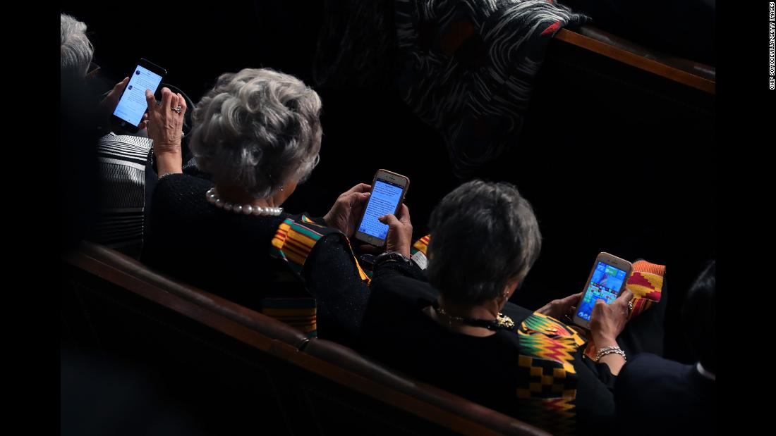 Members of Congress look at their cell phones during the State of the Union address on Tuesday, January 30.