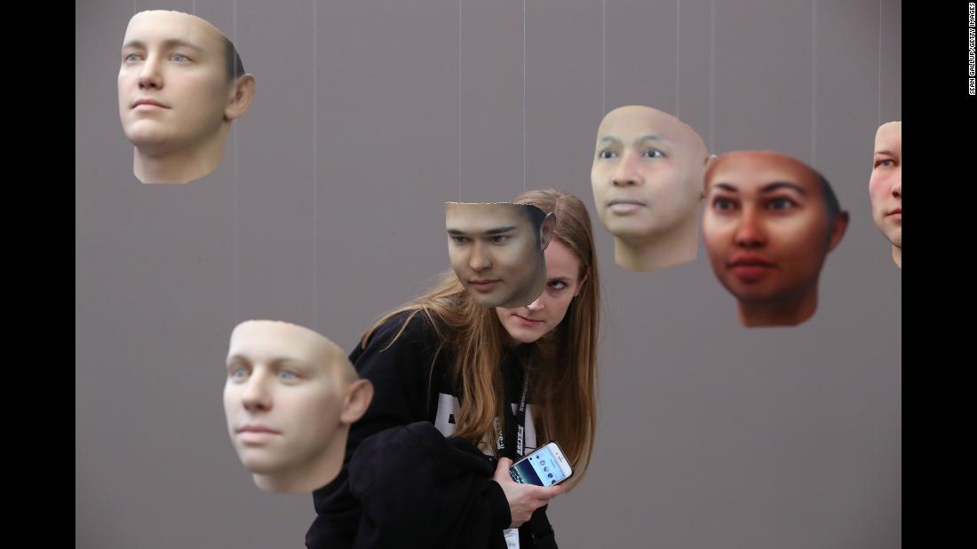 "A woman looks at 3D-printed faces, part of the installation ""A Becoming Resemblance,"" at an art show in Berlin on Wednesday, January 31. The installation, by artist Heather Dewey-Hagborg, is made up of 30 masks derived from Chelsea Manning's DNA. Manning is the former Army intelligence analyst who spent several years in prison for leaking classified information to WikiLeaks."