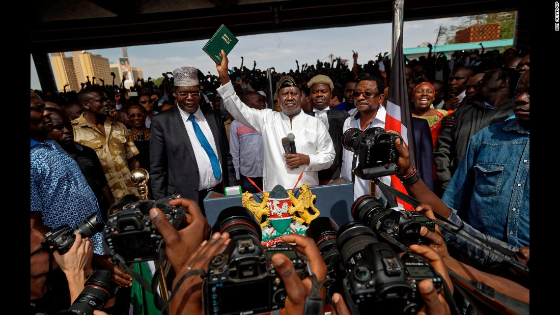"Kenyan opposition leader Raila Odinga, who boycotted the country's disputed election last year, holds a Bible during <a href=""https://www.cnn.com/2018/01/30/africa/kenya-raila-odinga-protest-intl/index.html"" target=""_blank"">a mock inauguration ceremony</a> in downtown Nairobi on Tuesday, January 30. He swore himself in as ""the people's president"" during the protest."