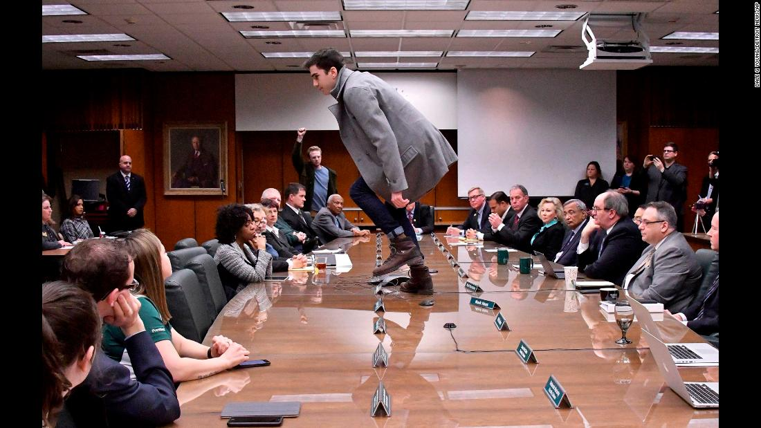 "Connor Berdy, a student from Michigan State University, climbs atop a table Wednesday, January 31, to protest the board of trustees' <a href=""https://www.cnn.com/2018/01/31/us/michigan-state-engler-president-nassar/index.html"" target=""_blank"">selection of John Engler</a> as the school's interim president. Engler is a former Michigan governor. Berdy complained to the board that the students didn't have a say in who the president would be after Lou Anna Simon, who resigned in the upheaval over <a href=""https://www.cnn.com/2018/01/31/us/larry-nassar-sentencing-eaton-county-michigan/index.html"" target=""_blank"">Larry Nassar's decades of abuse.</a>"
