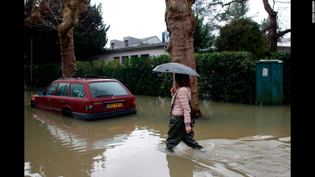 "A woman walks in a flooded street of Villennes-sur-Seine, France, on Tuesday, January 30. The rain-swollen Seine River burst its banks, leaving many towns flooded and <a href=""https://www.cnn.com/2018/01/27/europe/paris-flood-alert-peak-intl/index.html"" target=""_blank"">threatening Paris as well.</a>"
