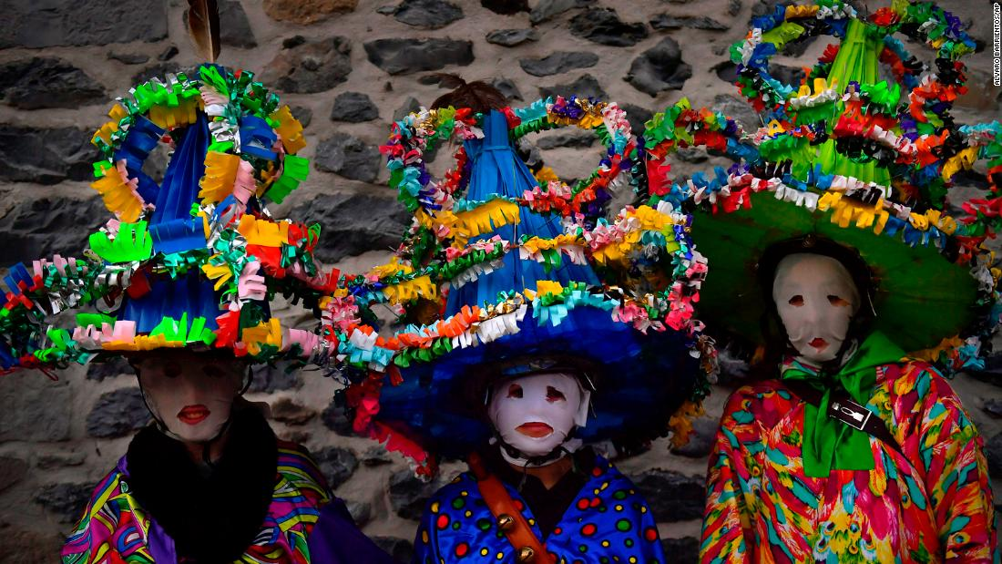 People wear traditional clothes and large hats as they take part in the Carnival of Leitza, Spain, on Tuesday, January 30.