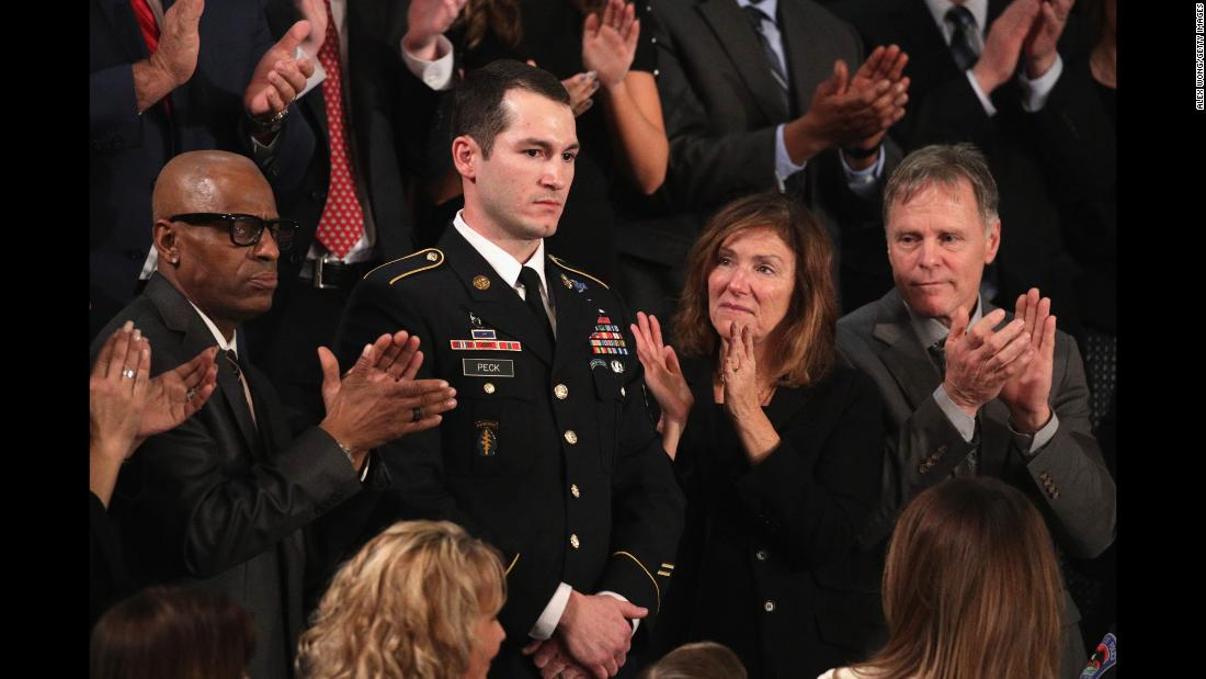 "Army Staff Sgt. Justin Peck is acknowledged during President Donald Trump's <a href=""https://www.cnn.com/2018/01/30/politics/state-of-the-union-2018/index.html"" target=""_blank"">first State of the Union address</a> in Washington on Tuesday, January 30. Peck helped save the life of his comrade, Chief Petty Officer Kenton Stacy, after Stacy was severely wounded during an explosion near Raqqa, Syria, last November, while Peck and Stacey were on a mission to clear buildings that ISIS had rigged with explosives. ""Kenton Stacy would have died if not for Justin's selfless love for a fellow warrior,"" <a href=""http://www.cnn.com/2018/01/30/politics/2018-state-of-the-union-transcript/index.html"" target=""_blank"">President Trump said</a>. ""Tonight, Kenton is recovering in Texas. Raqqa is liberated. And Justin is wearing his new Bronze Star, with a 'V' for 'Valor.' Staff Sergeant Peck: All of America salutes you."""
