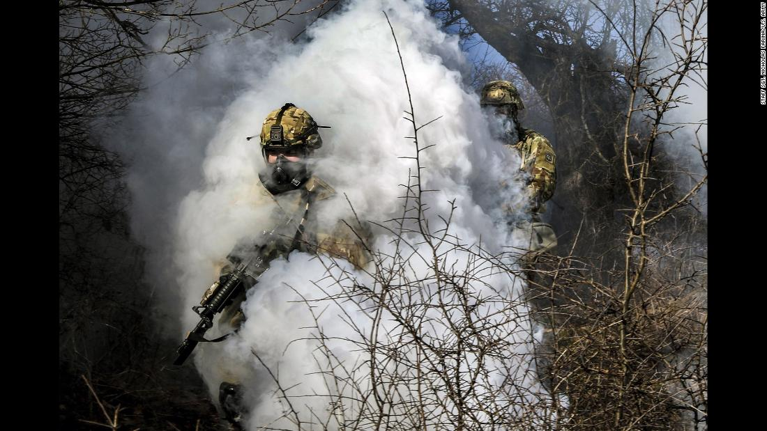 Soldiers walk through smoke from a grenade during an Operation Bowie Strike training exercise in Zhegoc, Kosovo, on Friday, January 19.