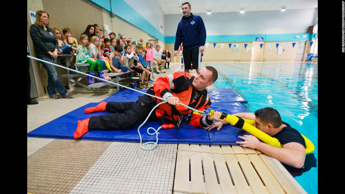 Petty Officer Connor Hallinan talks to children about ice safety as Coast Guard Fireman Thomas Chanady, center, and Petty Officer Matt Huber demonstrate icy water rescue techniques at the Benton Harbor-St. Joseph YMCA in St. Joseph, Michigan, on Tuesday, January 2.