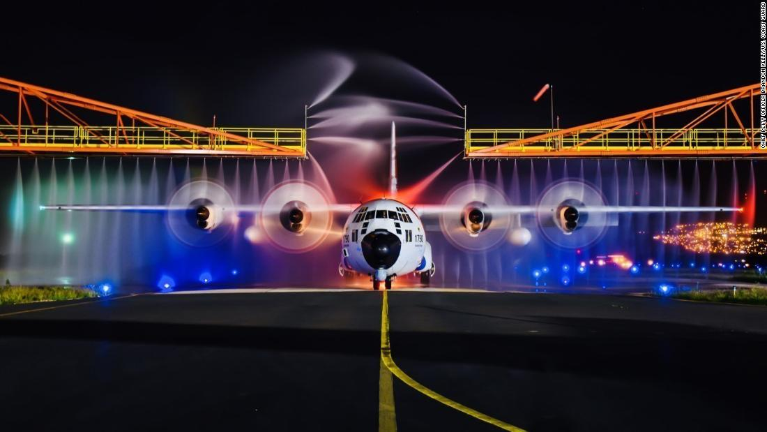 A Coast Guard HC-130 Hercules aircraft is rinsed down at Air Station Barbers Point in Honolulu County, Hawaii, on Tuesday, January 2. Crew members maintain operational readiness by washing the plane after every flight to protect it and remove any salt.