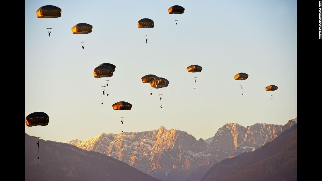 Army paratroopers descend from an Air Force 86th Air Wing C-130 Hercules aircraft onto Juliet Drop Zone during an airborne operation in Pordenone, Italy, on Thursday, January 18.