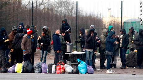 Migrants take a coffee and food provided by activists in Calais, northern France.