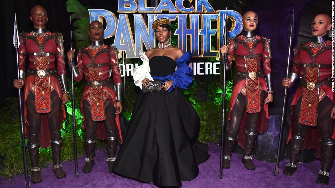 Singer and actor Janelle Monae looking charming in a black Christian Siriano gown with billowing white and blue sleeves. She completes the look with a golden crown and colorful African beads worn around her neck.