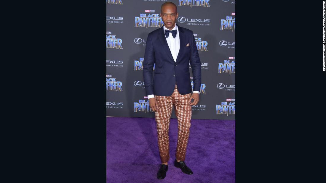 Actor J. August Richards attends the premiere in dark blue blazer and ankara-patterned trousers.