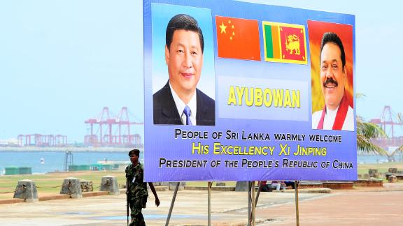 A Sri Lankan soldier walks past a billboard bearing portraits of Chinese President Xi Jinping and Sri Lankan President Mahinda Rajapakse, ahead