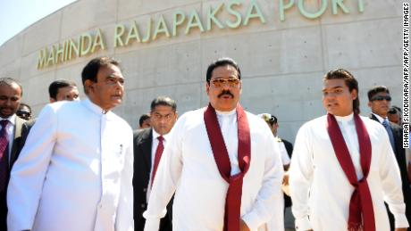 Sri Lanka's President Mahinda Rajapakse, center, flanked by his eldest son and parliamentarian Namal Rajapakse, right, and Prime Minister D. M. Jayaratne, left, tour the Hambantota construction site, November 18, 2010.