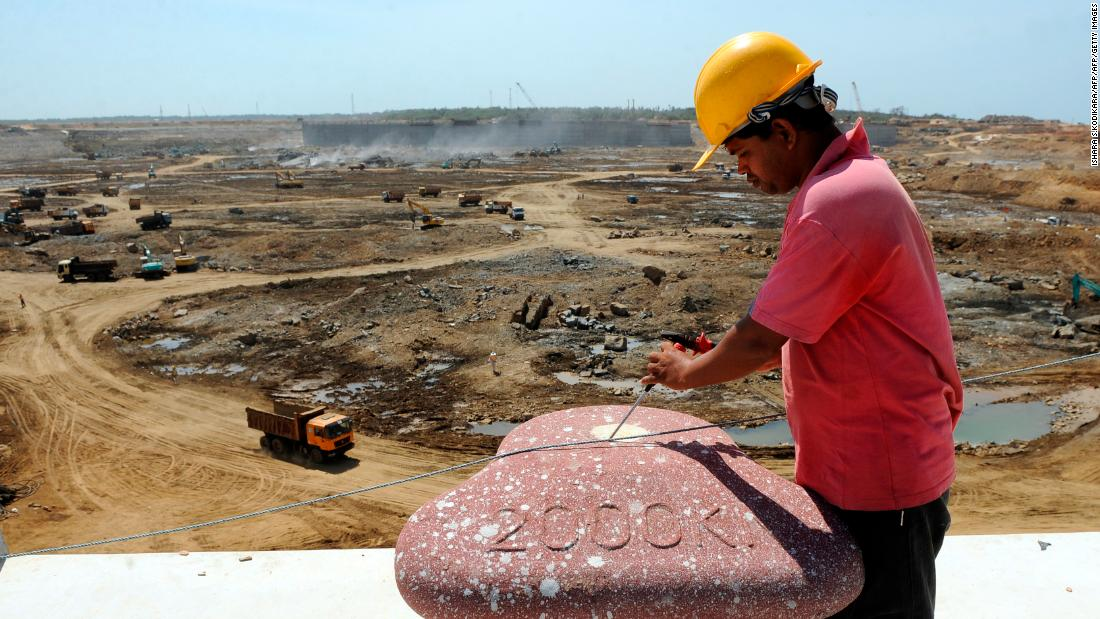 Construction workers operate heavy equipment at the base of Sri Lanka's Hambantota port August 1, 2010. Some 350 Chinese staff helped in the first phase of construction.