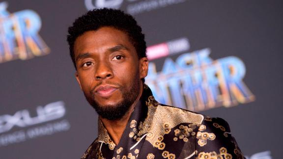 Chadwick Boseman is T'Challa (Black Panther), the king of Wakanda. His outfit is a silky black Emporio Armani jacket with intricate golden floral patterns.
