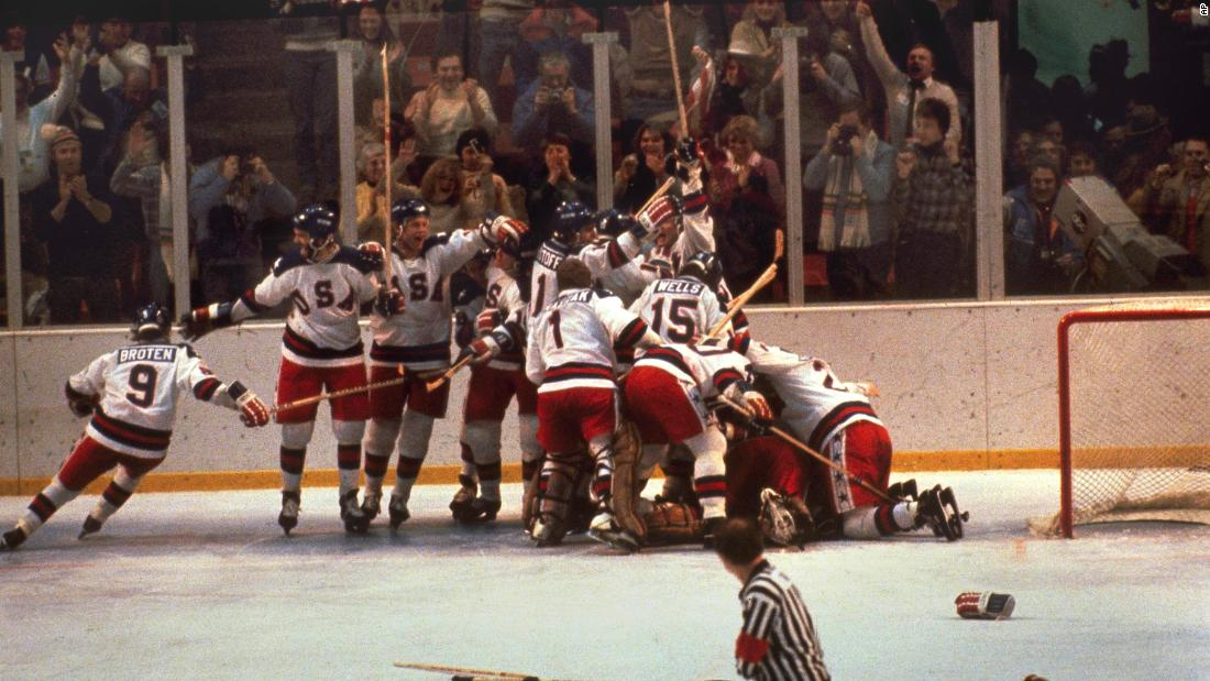 The US hockey team pounces on goalie Jim Craig after a 4-3 victory against the Soviets in the 1980 Olympics, as a flag waves from the partisan Lake Placid, N.Y. crowd, February 22, 1980.