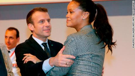 "French President Emmanuel Macron embraces singer Rihanna as they attend the conference ""GPE Financing Conference, an Investment in the Future"" in Dakar on February 2, 2018, as part of Macron's visit to Senegal."