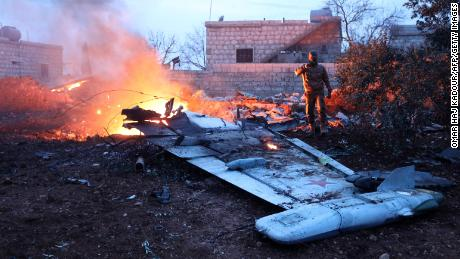 TOPSHOT - A picture taken on February 3, 2018, shows a Rebel fighter taking a picture of a downed Sukhoi-25 fighter jet in Syria's northwest province of Idlib. Rebel fighters shot down a Russian plane over Syria's northwest Idlib province and captured its pilot, the Syrian Observatory for Human Rights said.   / AFP PHOTO / OMAR HAJ KADOUR / The erroneous mention[s] appearing in the metadata of this photo by OMAR HAJ KADOUR has been modified in AFP systems in the following manner: [in Syria's northwest province of Idlib.] instead of [near the Syrian city of Saraqib, southwest of Aleppo.]. Please immediately remove the erroneous mention[s] from all your online services and delete it (them) from your servers. If you have been authorized by AFP to distribute it (them) to third parties, please ensure that the same actions are carried out by them. Failure to promptly comply with these instructions will entail liability on your part for any continued or post notification usage. Therefore we thank you very much for all your attention and prompt action. We are sorry for the inconvenience this notification may cause and remain at your disposal for any further information you may require.        (Photo credit should read OMAR HAJ KADOUR/AFP/Getty Images)