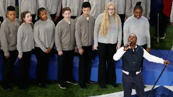 """Leslie Odom Jr. is backed up by children as he sings """"America the Beautiful."""""""