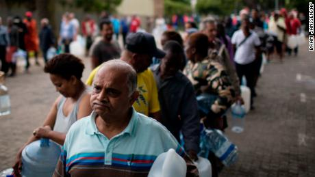 "Residents queue to fill containers with water from a source of natural spring water in Cape Town, South Africa, Friday, Feb. 2, 2018. South Africa's drought-hit city of Cape Town introduced new water restrictions in an attempt to avoid what it calls ""Day Zero,"" the day in mid-April when it might have to turn off most taps. (AP Photo/Bram Janssen)"