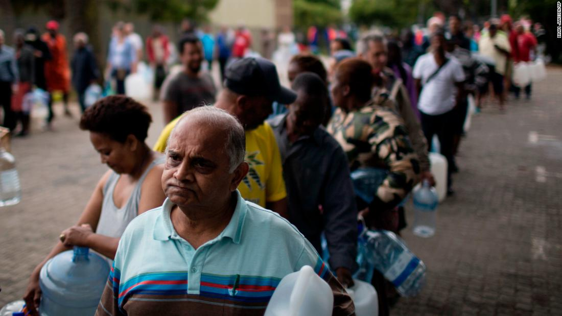 "Residents queue to fill containers from a source of natural spring water in Cape Town, South Africa, February 2. The drought-hit city introduced new water restrictions in an attempt to avoid what it calls ""Day Zero,"" the day in mid-April when it might have to turn off most taps."