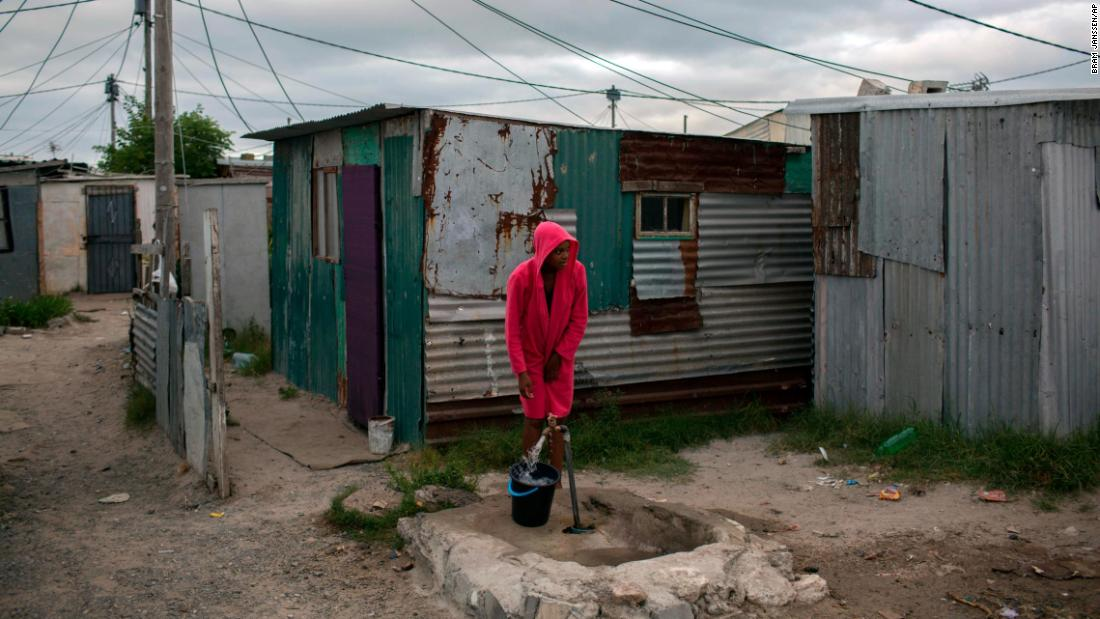 A woman collects water in a settlement near Cape Town on Friday, February 2.