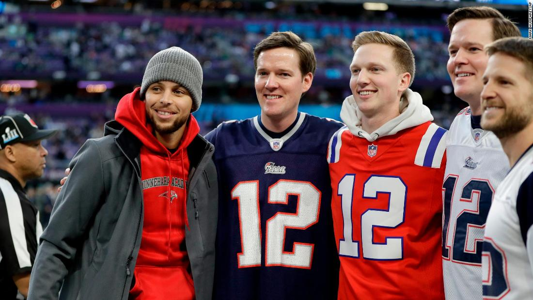Basketball star Stephen Curry, left, poses for a photo with Patriots fans.