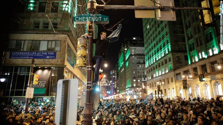 A man climbs a traffic pole as Philadelphia Eagles fans celebrate victory.