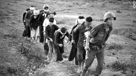 A string of ten blindfolded Viet Cong suspects is led to his base camp by a soldier of the Korean Tiger division on Feb. 20, 1966.