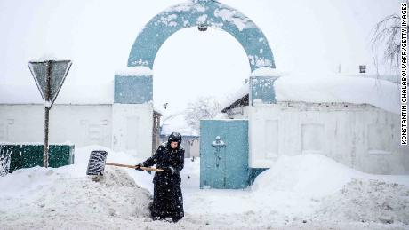 A nun shovels snow in front of a nunnery in the village of Bogoslovo, 190km outside Moscow.