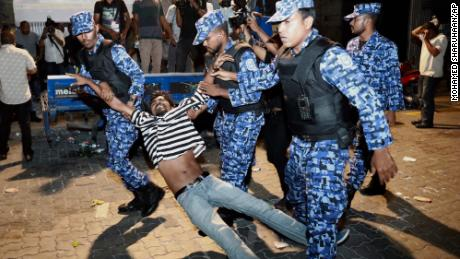 Maldivian police officers detain an opposition protestor demanding the release of political prisoners.