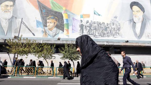 An Iranian woman walks past pictures of Iranian supreme leader Ayatollah Ali Khamenei (top L) and of late Iranian supreme leader Ayatollah Ruhollah Khomeini (top R), on October 13, 2017.