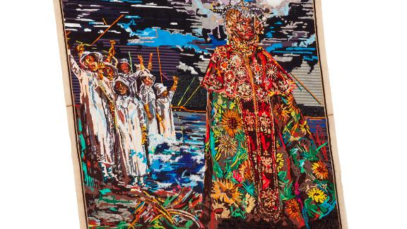 """The bulk of the exhibition is made up of hand-embroidered tapestries. By creating quasi-historical artifacts, such as maps, portraits and tapestries showing mythological events, Ruga is forming his own nation, Azania. This piece is entitled """"Somagwaza: a Queen's Herald."""""""