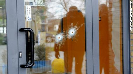 Bullet holes are seen in a glass door as police forensics officers carry out investigations in the area following the wounding of several foreign nationals in a drive-by shooting at Macerata, on February 3, 2018 Italian police said they have arrested a man suspected of opening fire on foreigners from a vehicle in central Italy on February 3, 2018. Media reported six people were injured, four of them seriously, in the incident in the town of Macerata.   / AFP PHOTO / STR        (Photo credit should read STR/AFP/Getty Images)