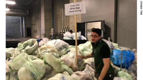 US Bank Stadium Sustainability Coordinator Bradley Vogel places a sign in the middle of a pile of trash bags for sorting on Monday. Green bags were for composting and white bags for waste.